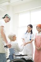 介護老人を診察する医者と介護士
