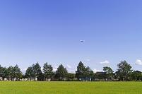 北海道 公園の広場と飛行機飛ぶ青空