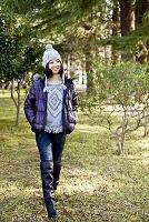 公園を散歩する毛糸の帽子とダウンジャケットを着た日本人女性
