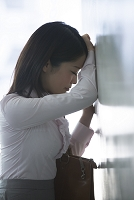 ガード下で落ち込むビジネス女性