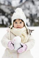 雪山でミニ雪だるまを持つ子供の子供