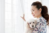 犬を抱く笑顔の日本人女性