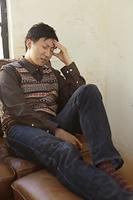 ソファーで頭を押さえる体調不良の男性