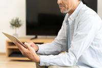 iPadを操作するする中年男性