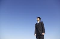 青空を見上げるスーツの若い男性