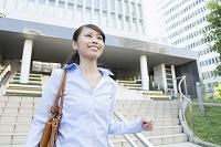 ビルの階段を駆け下りるビジネス女性