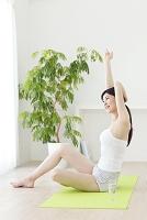 ヨガマットの上でくつろぐ若い日本人女性をする女性