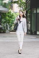 ビジネス街を歩く女性 タンブラーを持つ