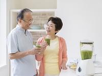 野菜ジュースを持つシニア夫婦