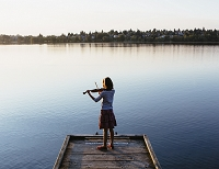 桟橋でヴァイオリンを弾く少女