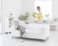 ソファに座る夫とジョウロを持つ妻