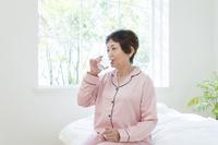 ベッドに水を飲むパジャマ姿の日本人のシニア女性
