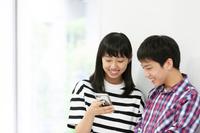 スマートフォンを見る中学生