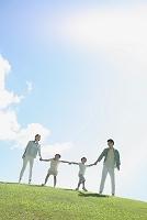 芝生と手を繋ぐ日本人家族