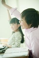 教室で挙手する日本人の小学生の男の子と女の子