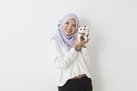 招き猫の置物を持つムスリムの女性