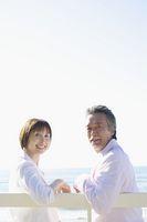 海辺のベンチに座るシニア夫婦