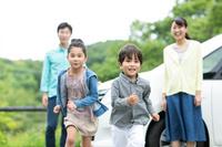 走る子供を見守る両親