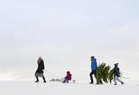 雪の中を並んで歩く家族