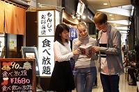 外国人カップルに日本料理店の案内をする日本人