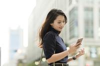 街でスマホを見る日本人女性