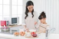 料理をする女の子と母親