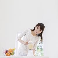 ミキサーでジュースを作る女性