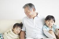 ソファに座る孫と笑顔の祖父