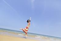 海辺でジャンプする日本人女性