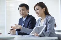 タブレットを見せる日本人ビジネスウーマン