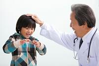 男の子の頭を撫でている中高年医師