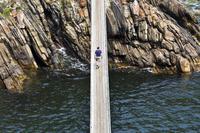 橋を渡る男性 海