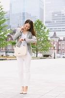 電話する日本人女性 東京駅前