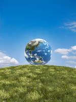 青空バックの草原の丘に地球