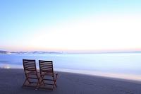 神奈川県 波打ち際の砂浜に置かれた椅子と夜明けの空