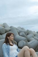 テトラポッドに座って音楽を聴く日本人女性