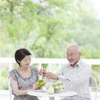 テラスで食事をするシニア夫婦