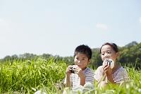 田園でおにぎりを食べる男の子と女の子