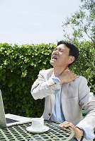 肩こりに顔をゆがめる中年日本人男性