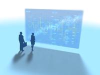 株価進捗を示すGUIパネルを眺めるビジネス男女