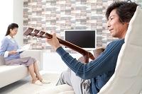 ギターを弾く男性と本を読む日本人女性