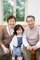 ソファに座って微笑む祖父母と孫