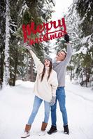 クリスマスメッセージを掲げるカップル
