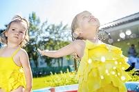 庭で水遊びをする子供たち