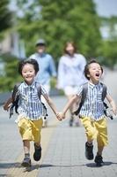 手を繋いで走る日本人の双子