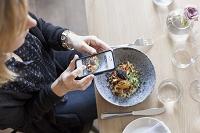 スマートフォンで料理を撮影する女性