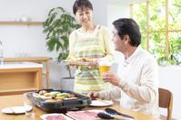 焼肉を食べる中高年夫婦