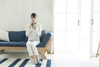 ソファに座ってスマホを操作する若い日本人女性