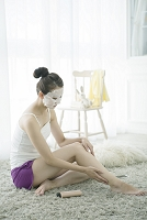 フェイスパックをしながらボディクリームを塗る20代日本人女性