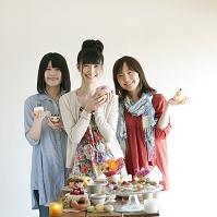 お菓子を持ち微笑む日本人女性